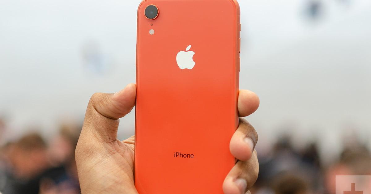 Smartphone iPhone XR de color naranja sujetado por un hombre