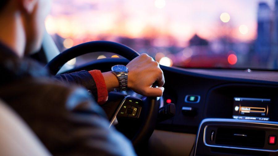 Joven abordo de un auto manejando en carretera.