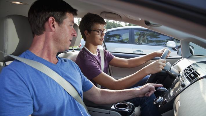 Joven adolecente siguiendo indicaciones de un adulto al manejar.