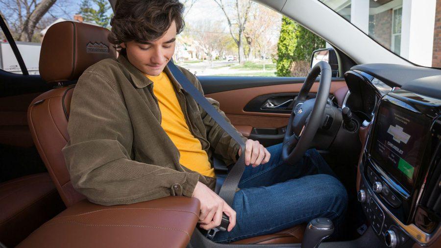 Joven abrochándose su cinturón de seguridad arriba de su auto.