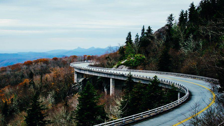 Carretera en curva entre las montañas llenas de árboles.