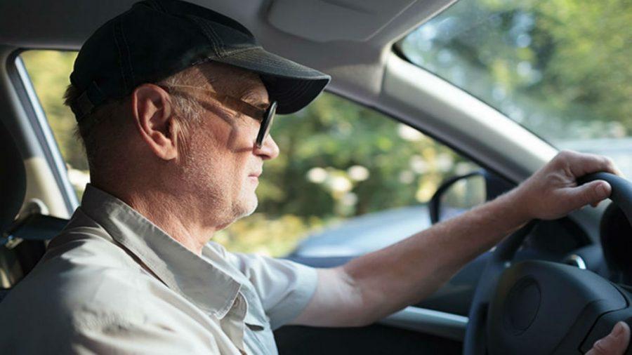 Adulto mayor manejando un auto.